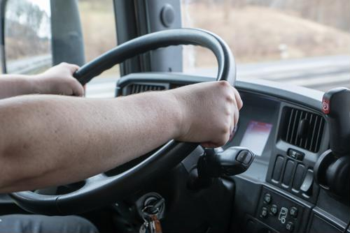 Truck steering wheel with driver's hand.