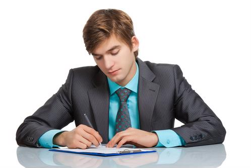 Man in suit filling out paperwork