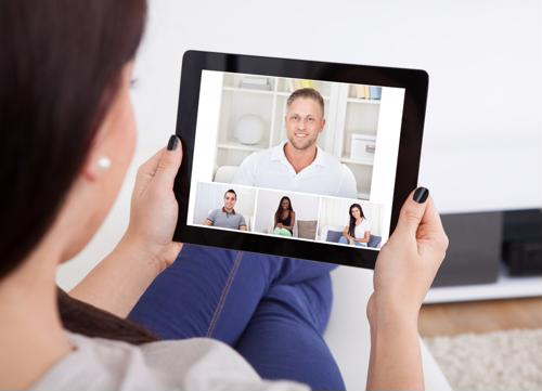A woman holds a tablet for a video call with four other people.